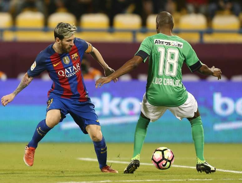 FC Barcelonas Lionel Messi (L) vies with Al-Ahlis Luiz Carlos during a friendly. AFP