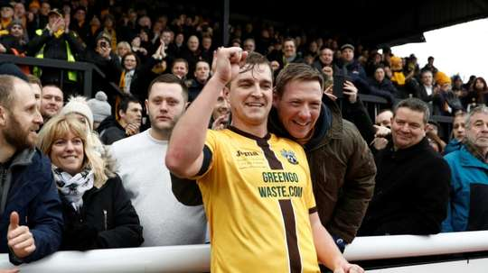 Sutton United's Jamie Collins celebrates with supporters. AFP