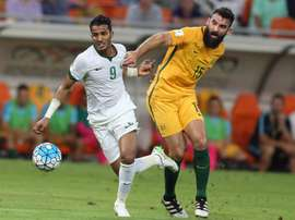Australias Mile Jedinak (R) marks Saudi Arabias Nawaf Alabid during a 2018 FIFA World Cup qualifying match in Jeddah on October 6, 2016