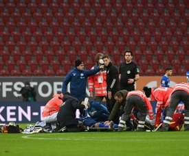 Medics tend to Schalke striker Mark Uth after a frightening clash of heads. AFP