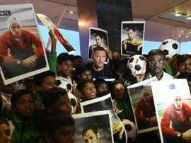 Italian footballer Marco Materazzi (top C) poses with football fans who had gathered at the Kempegowda International Airport to welcome him on his arrival in Bangalore on September 20, 2014