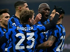 Inter Milan midfielder Arturo Vidal (R) and Nicolo Barella (C) celebrate after scoring.AFP