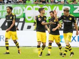 Dortmund players celebrate scoring the opening goal during the Bundesliga match against Wolfsburg