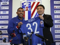 Argentine striker Carlos Tevez (L) poses with his No. 32 shirt of his new club Shanghai Shenhua. AFP