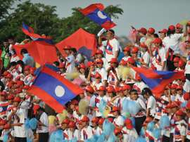 Laos supporters wave national flags during a football match in Vientiane