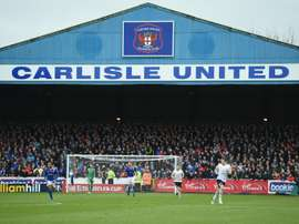 Fans line the terraces behind the goal during the English FA Cup fourth round football match between Carlisle United and Everton at Brunton Park, in Carlisle, north west England, on January 31, 2016
