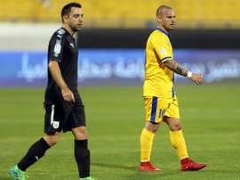 Xavi beats Sneijder - this time in Qatar. AFP