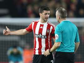 Southamptons striker Shane Long (L) talks with referee Jon Moss during an English Premier League football match against Arsenal on December 26, 2015