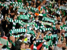 Celtic fans raise their scarves in the crowd at a match in Glasgow, Scotland on October 1, 2015