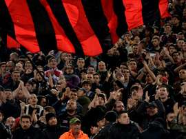 AC Milans fans cheer during the Italian Serie A football match between Lazio and AC Milan at Olympic Stadium in Rome on November 1, 2015