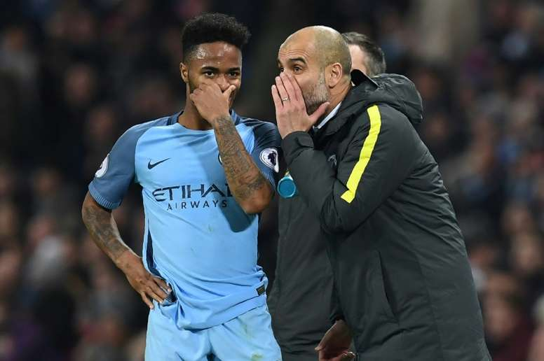 Manchester City manager Pep Guardiola (R) talks to midfielder Raheem Sterling. AFP
