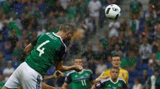 Northern Ireland defender Gareth McAuley (L) scores the opening goal against Ukraine. BeSoccer