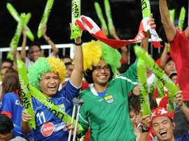 Supporters for the Lions XII team cheer during a football match in Singapore on January 10, 2012
