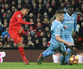 Liverpools midfielder Roberto Firmino (L) scores Liverpools second goal during the English Premier League football match between Liverpool and Stoke City at Anfield in Liverpool, north west England on December 27, 2016