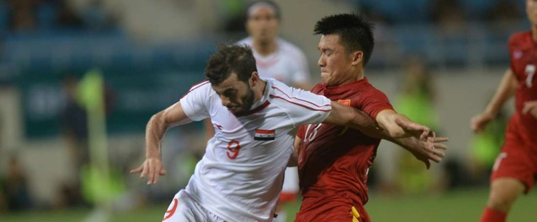 Syrias Mahmoud Al-Mawas (L) fights for the ball with Vietnams Tran Dinh Dong during a friendly at Hanois My Dinh stadium on May 31, 2016