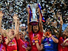 Olympique Lyonnais captain Wendie Renard holds the trophy to celebrate with teammates after winning the UEFA Womens Champions League Final football match VFL Wolfsburg vs Lyon in Reggio Emilia, Italy on May 26, 2016
