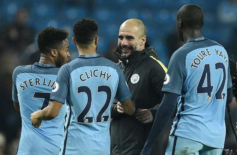 Manchester Citys manager Pep Guardiola (C) congratulates Raheem Sterling (L), Gael Clichy (2ndL) and Yaya Toure on December 18, 2016