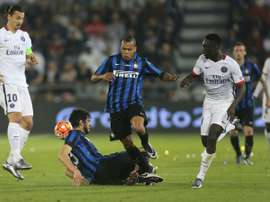Paris Saint-Germain forward Jean-Kevin Augustin (R) fights for the ball with Inter Milans Jonathan Biabiany (C) during the friendly football match in Doha, on December 30, 2015