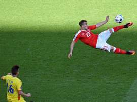 Switzerland midfielder Xherdan Shaqiri (R) kicks the ball against Romania. BeSoccer