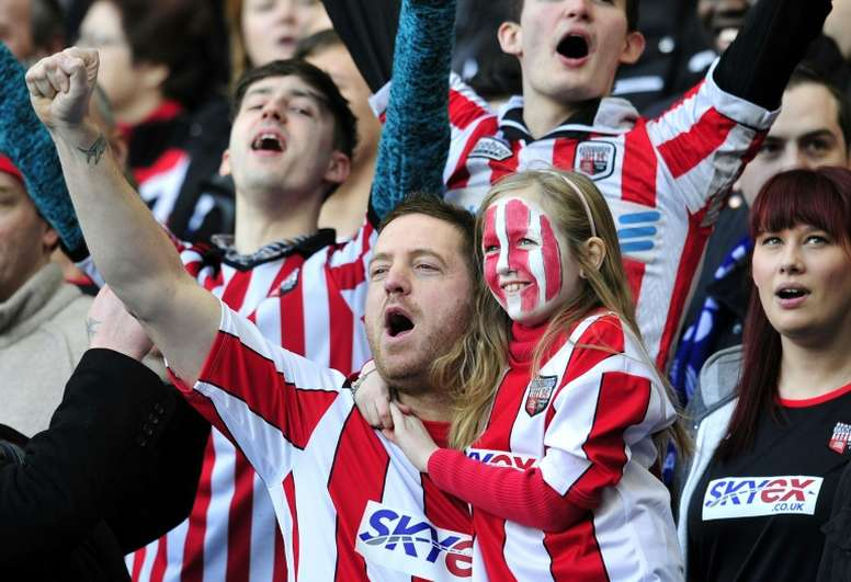 Brentford supporters cheer for their team during the fourth round replay English FA Cup football match between Chelsea and Brentford at Stamford Bridge in London on February 17, 2013