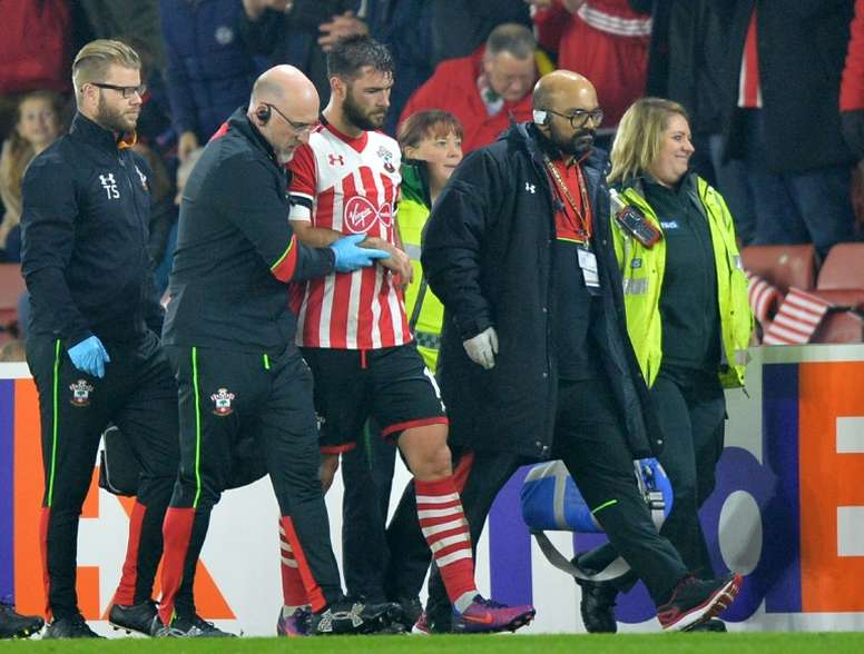 Southamptons striker Charlie Austin (C) is helped from the pitch after picking up an injur. AFP