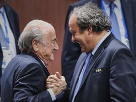 FIFA President Sepp Blatter (L) shaking hands with UEFA President Michel Platini in Zurich on May 29, 2015