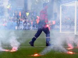A fire fighter extinguish flares lobed onto the pitch during the Euro 2016 group D football match between Czech Republic and Croatia at the Geoffroy-Guichard stadium in Saint-Etienne on June 17, 2016