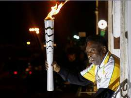 Former football player Pele holds the Olympic flame at the Pele Museum in Santos, Sao Paulo State, Brazil, on July 22, 2016