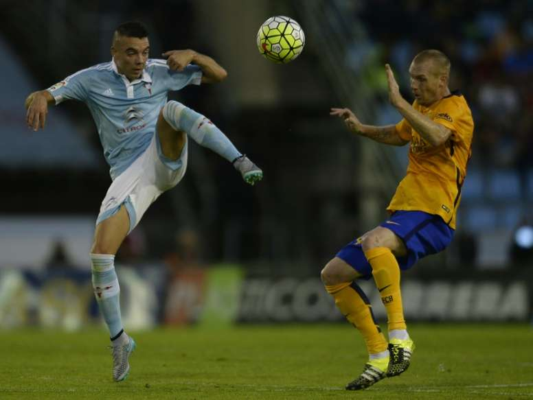 Celta Vigos Iago Aspas (L) fights for the ball with Barcelonas Jeremy Mathieu during their Spanish La Liga match, at the Balaidos stadium in Vigo, on September 23, 2015