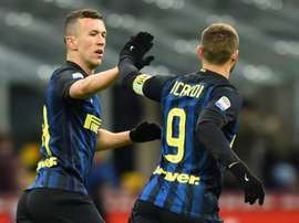 Inter Milans Argentina Mauro Icardi (R) celebrates with teammate Ivan Perisic after scoring a goal against Chievo in Milan on January 14 , 2017