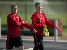 Manchester Uniteds Wayne Rooney (L) and Bastian Schweinsteiger arrive to take part in a team training session at their Carrington training complex in Manchester, England on September 29, 2015