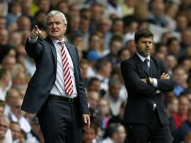 Tottenham Hotspurs Argentinian Head Coach Mauricio Pochettino (R) and Stoke Citys Welsh manager Mark Hughes (L) watch from the touchline during the English Premier League football match at White Hart Lane in north London on August 15, 2015