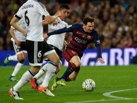 Barcelonas forward Lionel Messi (R) fights for the ball with Valencias midfielder Enzo Perez on April 17, 2016