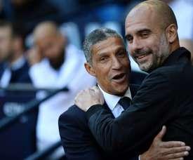 Pep Guardiola greets Brighton manager Chris Hughton. AFP