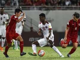 Qatars Mohammed Muntari (C) dribbles the ball past Hong Kongs Huang Yang (R) during their 2018 World Cup football qualifying match in Hong Kong on September 8, 2015