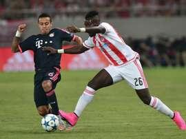 Le défenseur Français de l'Olympiakos Arthur Masuaku à la lutte avec Thiago Alcantara, du Bayern.