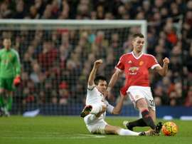 Manchester Uniteds midfielder Morgan Schneiderlin (R) is tackled by Swansea Citys midfielder Jack Cork during the English Premier League football match January 2, 2016