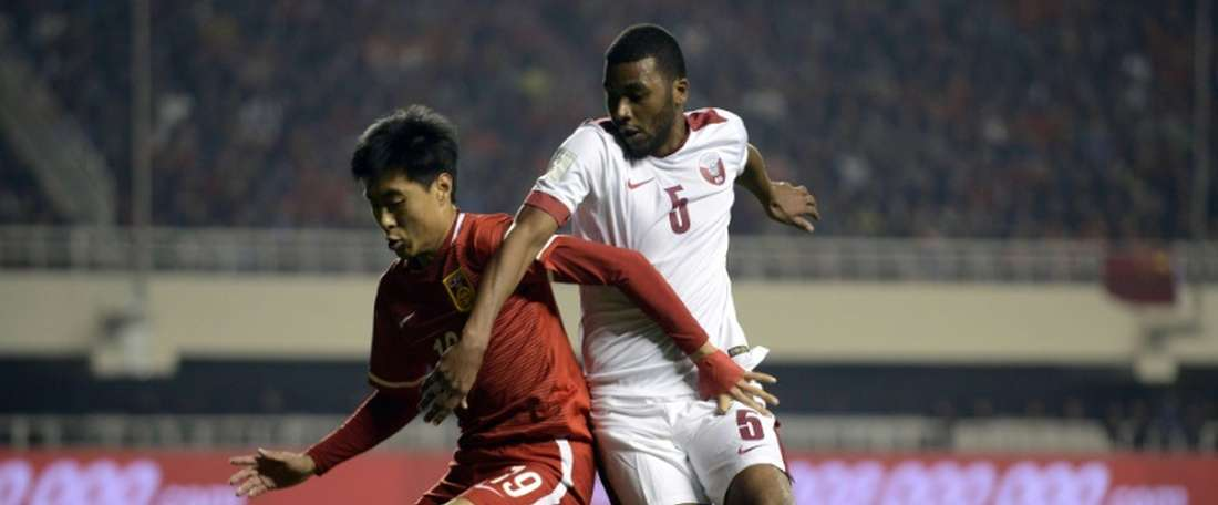 Jiang Ning (left) of China competes for the ball with Abdelaziz Hatim of Qatar during their 2018 World Cup football qualifying match in Xian, northwest Chinas Shanxi province on March 29, 2016