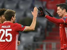 Lewandowski (R) celebrates scoring his 71st Champions League goal. AFP