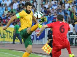 Australias Mile Jedinak (L) and Kyrgyzstans Viktor Maier during the FIFA World Cup 2018 Group B qualifying match in Bishkek on June 16, 2015