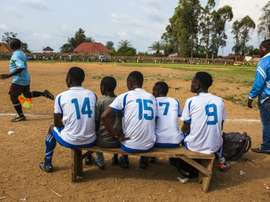 Local football players follow a match from the bench in Beni, DR Congo. AFP