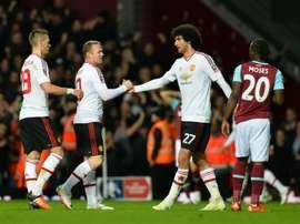 Manchester Uniteds striker Wayne Rooney (2ndL) congratulates midfielder Marouane Fellaini (C) after winning the FA cup quarter final replay on April 13, 2016