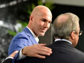 Real Madrids new coach Zinedine Zidane (L) is congratulated by Real Madrids president at the Santiago Bernabeu stadium in Madrid on January 4, 2016