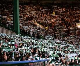 Celtic fans hold aloft scarves at Celtic Park stadium in Glasgow. AFP
