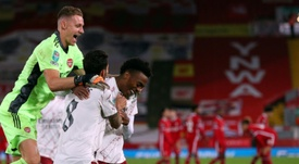 Arsenal goalkeeper Bernd Leno (L) celebrates with Joe Willock (R). afp_en