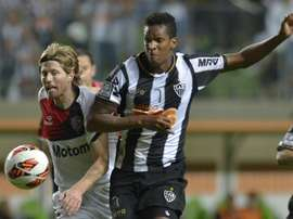 Milton Casco (left), of Argentinas Newells Old Boys, vies for the ball with Jo, of Brazils Atletico Mineiro, during their 2013 Copa Libertadores second leg semifinal football match at Arena Independencia Stadium in Belo Horizonte, on July 10, 2013