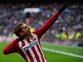 Atletico Madrids forward Antoine Griezmann celebrates after scoring during the Spanish league football match Real Madrid CF vs Atletico de Madrid at the Santiago Bernabeu stadium in Madrid on February 27, 2016