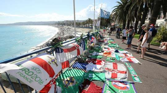 People stand next to tributes for a Northern Ireland fan who died during the Euro 2016 football tournament in Nice
