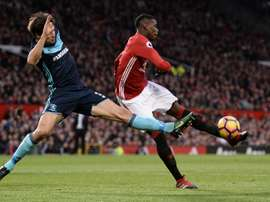 Manchester Uniteds midfielder Paul Pogba (R) attemps to shoot past Middlesbroughs defender George Friend during the English Premier League football match at Old Trafford in Manchester, north west England, on December 31, 2016