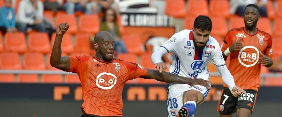 Lyon's Nabil Fekir (C) vies with Lorient defender Michael Ciani. AFP